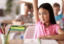Girl raising hand in class.