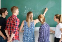A group of students watching a teacher draw a graph on a blackboard.