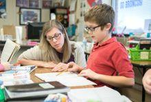 Elementary school teacher helping student in classroom.