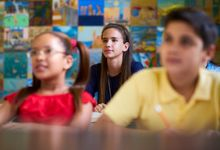 Smart Girl Listening to Teacher At School