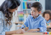 Young schoolboy works with his teacher at school