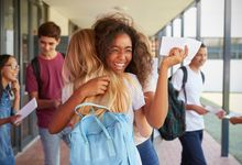 Two high school girls hug in the school hallway, celebrating their report cards
