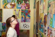 A middle school student attending a student art show, looking at her classmates' art on the wall