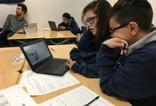 Two students looking at data on a laptop with worksheets scattered in front of them