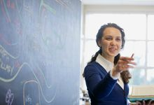 Teacher standing next to a blackboard that has a diagram drawn on it. She is pointing off-camera.