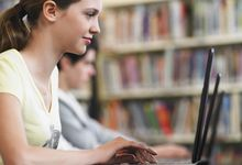 Students use laptops in the library