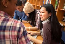 A group of students working on an essay in the library together