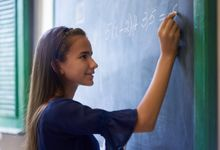 A middle school student doing algebra on a blackboard