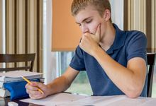 A teenage student studying at home at the dining table