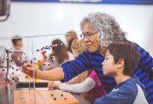 A teacher helping a student with an atom model