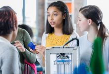 A group of students working with a 3D printer