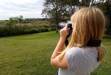 A student using a DSLR camera to photograph a landscape of a field and trees