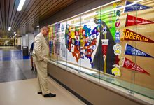 Principal Jeff Walters looks at a wall of college banners.