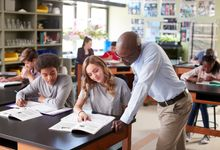 A teacher helping a student with a worksheet in science lab