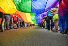 Under a LGBT Pride Flag