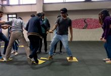 A group of teenagers doing an icebreaker exercise in which one person is blindfolded and the others are helping him jump across yellow tiles that are scattered across the floor