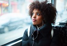 A woman rides a city bus, listening to a podcast on her headphones