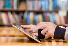 A close-up on a student's hands holding a tablet computer in a library