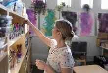 A teacher organizes shelves full of school supplies in her classroom