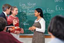 A teacher helping two Spanish language learners speak with each other in class