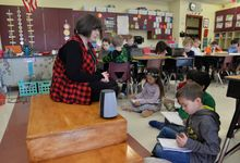 A teacher working with elementary students, who are writing in notebooks near a smart speaker device in a classroom