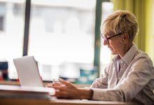 A teacher using her laptop in a classroom