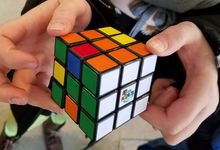 A pair of hands holding a Rubiks cube