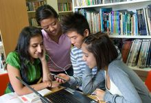 Group of senior teenage students together using portable audio player with a laptop computer in school reference library