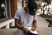 Male student sitting outside writing in a notebook