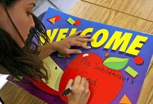 Elementary school teacher creating a welcome sign