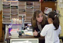 Teacher bending over talking to elementary student