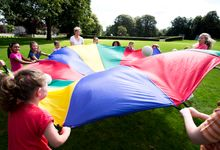 Teacher and students playing with parachute outside