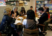 A group of teachers sitting, participating in a group discussion