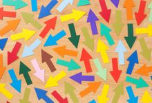 Multicolored paper arrows arranged in various directions on a wooden tabletop