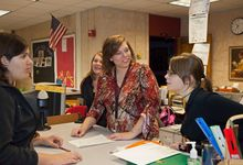 high school teacher speaks with students during a lesson