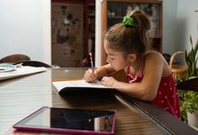 Young girl working on homework at her kitchen table