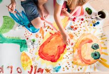 Kids painting together on a large piece of paper