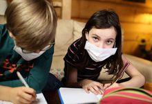 Children doing homework at home in masks during quarantine covid-19