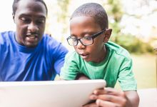 A father and son looking at computer screen outside