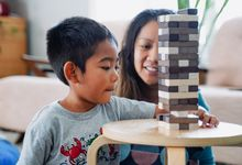 Young boy playing the game Jenga with his mother at home