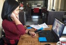 Woman participating in a group video meeting at home