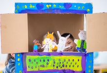 Children putting on a puppet show at home