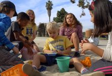 A group of fourth-grade students play with a peer with special needs in a sandbox during a field trip to a local playground in southern California.