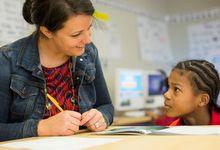 Elementary school teacher working with student