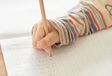 Close up of child's hand as they do math work in notebook.