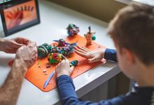 Boy working on a project with modeling clay with his father