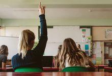 High school student raises hand in class.