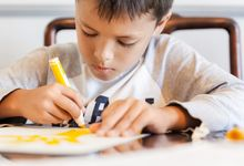 Boy drawing a picture with markers