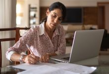 Woman working on her laptop and taking notes at home