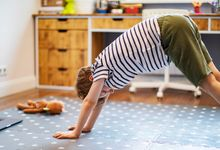 Young boy does yoga virtual class with laptop at home